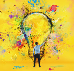 Fototapete - Boy draws with a brush a big light bulb. Concept of innovation and creativity. Yellow style