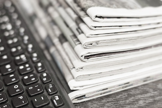 Concept for Journalism - Lots of Newspapers and Magazines Stacked in Pile and Computer Keyboard. News and Business Data in Tabloid Journals