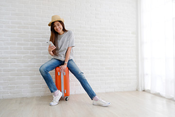 Young asian woman sitting on luggage holding smartphone in white room background, Happy teenage girl tourist in casual sit on travel luggage, suitcase, baggage ready for holiday vacation journey