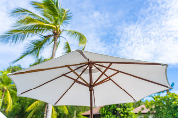 Selective focus point on umbrella with coconut palm tree on the background for holiday vacation