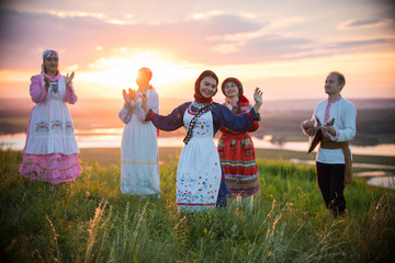 People in traditional russian clothes standing on the field on a background on the bright sunset - a woman dancing Wall mural