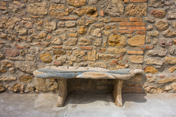 Bench made of stone in front of old stone wall, detail from streets of Voltera in Tuscany, Italy