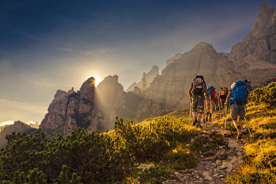 Some hikers go up a mountain path in the early hours of the day