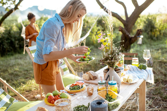 Woman eating healthy salad on a picnic in the beautifully decorated garden on a summer evening