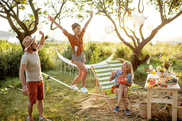 Young friends having fun, walking on a slackline during a picnic in the beautifully decorated garden on a sunset