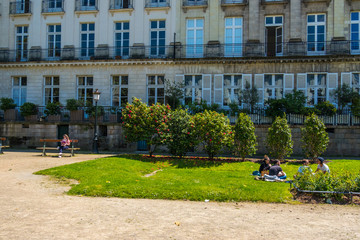 People rest on the lawn on Le Cours Cambronne square in Nantes, France
