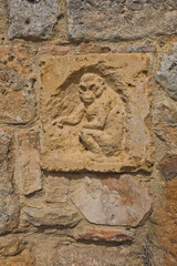 Artistic and architectural details on a wall at Volterra, Tuscany, Italy