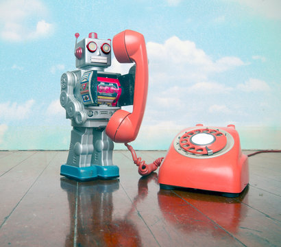 big silver robot toy on  a red phone standing on an old