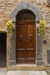 Sunflowers by the door at narrow winding street in city Voltera, Tuscany, Italy