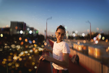 Bright summer lifestyle portrait of young pretty woman in eyewear, red skirt and white T-shirt, standing on the bright red bridge at evening with city background and blurred bokeh.