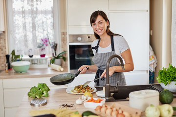 Caucasian woman in apron standing in kitchen and putting sauce on spaghetti.Preparation of italian food concept.