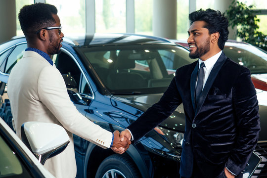 african-american salesman hand shake with indian buying customer at auto showroom