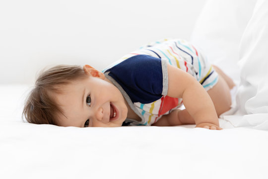 Portrait of laughing baby lying on bed looking at camera