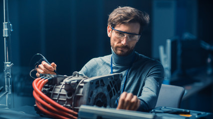 Professional Automotive Engineer in Glasses with a Computer and Inspection Tools is Testing an Used...