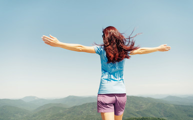 Active woman standing with raised arms in mountains.