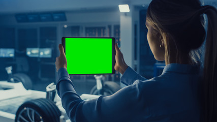 Female Engineer Holds a Tablet Computer with Green Screen Mock Up and Looks at Electric Car Chassis...