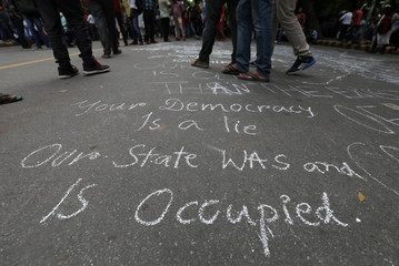 People stand on a road after drawing messages on it during a protest against the scrapping of the special constitutional status for Kashmir by the government, in New Delhi