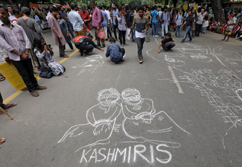 People draw and write messages on a road during a protest against the scrapping of the special constitutional status for Kashmir by the government, in New Delhi