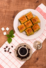 Turkish delights - baklava traditional sweets with turkish coffee, sugar the view from the top on wooden table and white fabric