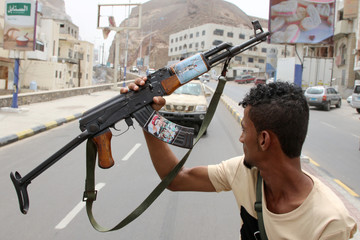 A member of Yemen's southern separatist holds his weapon with a picture of Muneer al-Yafee during a funeral of Brigadier General Muneer al-Yafee and his comrades killed in a Houthi missile attack, in Aden