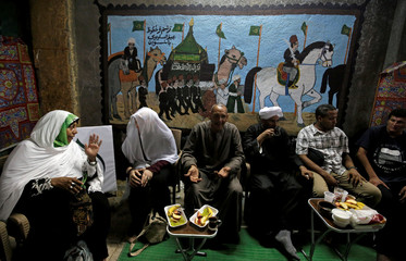 Men and women sit in front of murals painted by the artist Eid Al Salwaawi, who pictures murals showing the holy Kaaba and the rituals of the Hajj pilgrimage to Mecca, in Cairo