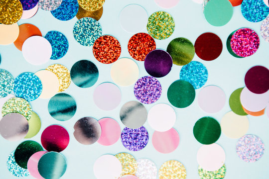 Colorful confetti explosion from envelope on blue background.
