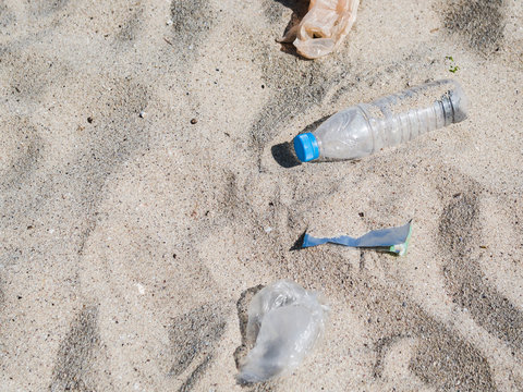 Overhead view of plastic trash on sand at beach
