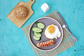 Breakfast, fried egg with sausage and slices of fresh cucumbers on a brown clay plate on a turquoise concrete background. Children's breakfasts. School breakfast concept. Top view, copy space.