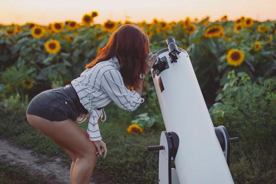 Sexy woman looking through telescope