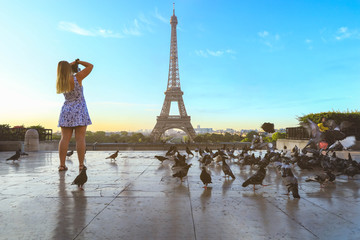 Tourist taking picture on eiffel tower with pigeons flying around