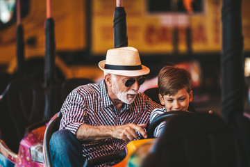 Grandfather and grandson having fun and spending good quality time together in amusement park. They enjoying and smiling while driving bumper car together.