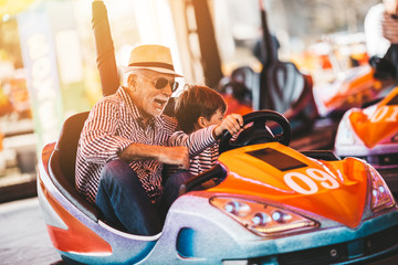 Papiers peints Attraction parc Grandfather and grandson having fun and spending good quality time together in amusement park. They enjoying and smiling while driving bumper car together.