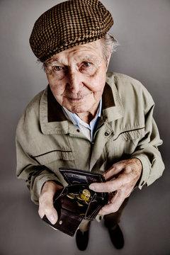 Portrait of senior man showing his purse