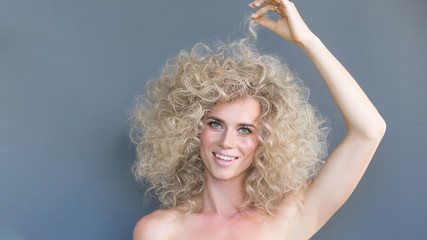 Portrait of a beautiful positive young blonde girl with blue eyes touching curls on her head posing on a gray background. Concept of unusual fashion image for taking pictures. crop 16:9