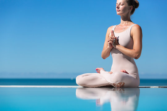 Sporty beautiful young woman practicing yoga, sitting in Easy Seat exercise, Sukhasana pose, working out, enjoying meditation session. Outdoor fcropp, blue water and sky background. Copy space