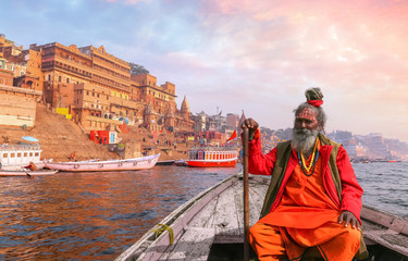 Indian Sadhu baba takes a boat ride on river Ganges overlooking the historic Varanasi city architecture at sunset Fotomurales