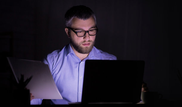 Caucasian man is working with papers, using laptop