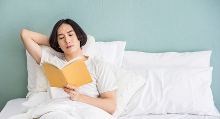 Portrait of handsome young asian man with enjoy reading book in white bed room modern apartment. Asian guy sleep resting, good night sleep, education sleepless concept panoramic banner