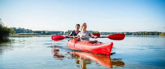 Happy couple kayaking on lake