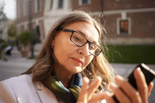 Close up view of attractive serious middle aged European woman wearing spectacles using touch pad mobile phone scrolling newsfeed via her social network account. Selective focus of female's face