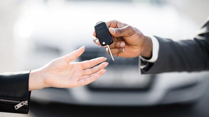 Car sale. Dealer giving key to new owner