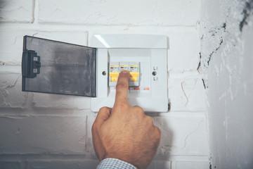 man hand turning off fuse box