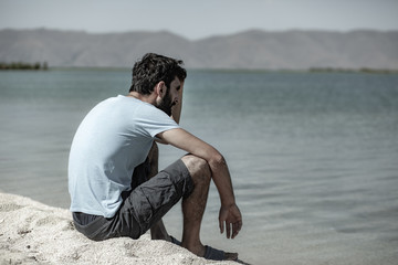 young man sitting on the shore