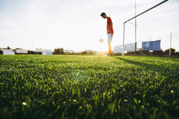 Soccer player on a football field training at sunset