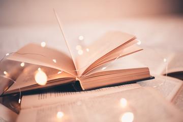 Open book with magic Christmas lights closeup. Good morning. Night time.
