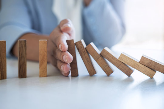 Risk and Strategy in Business, Image of hand stopping falling collapse wooden block dominoes effect from continuous toppled block, prevention and development to stability