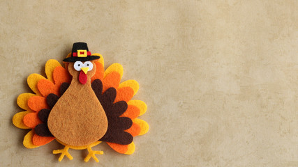 Felt turkey laying flat on a tan background with copy space