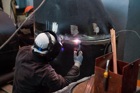 Welder welds steel pipe by gas tungsten arc welding