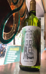 A bottle of Chateau Latif, each label hand-painted in watercolor around a design similar to the front of Latif Jiji's home on the Upper East Side in New York City