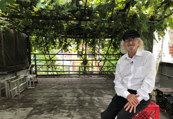 Vintner and retired engineering professor Latif Jiji poses on his rooftop surrounded by grapevines at his home on the Upper East Side in New York City